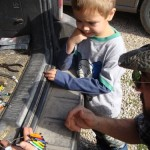 Three-year-old Connor of Clifton City watches Ethan with a Slate-colored Junco, and helps to pick out band colors.